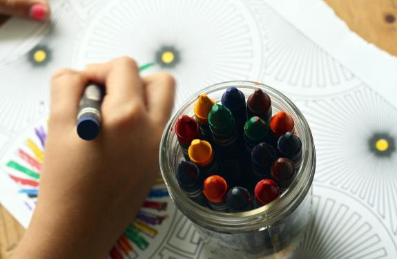 Pot of crayons with a hand drawing