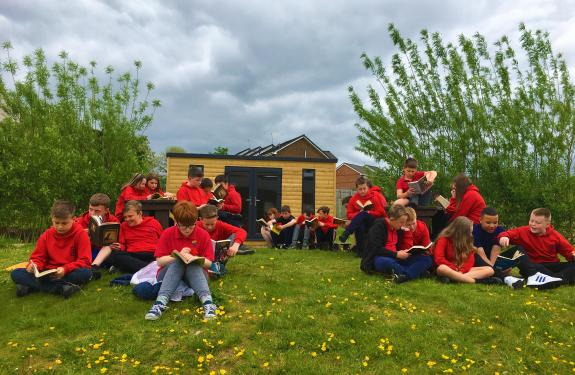 Crosshouse Primary School's P4-7 pupils reading outside in the playground.