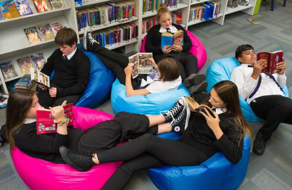 A photo of young people sitting on bean bags reading books