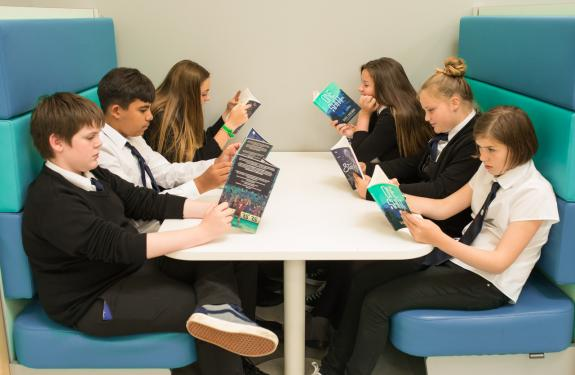 An image of young people reading at a table