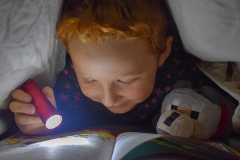 Young boy reads under a cover by torchlight